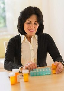 Woman sits and organizes her medication at a kitchen table