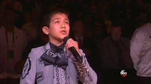 Sebastien De La Cruz holds microphone during his rendition of the National Anthem