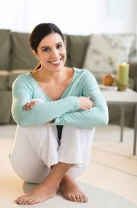 Woman sits on floor at home relaxed and smiling