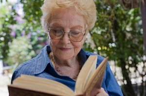 Older woman with glasses reads a book