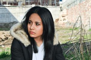 A saddened teen girl sitting outside