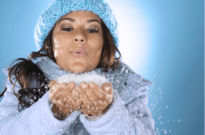 A woman blowing a pile of snow in her hands
