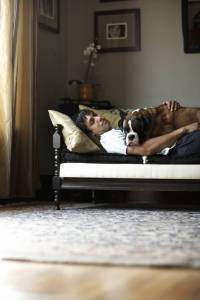 man with dog, sleeping with dog on couch