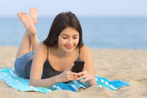 teen texting, teen using phone on the beach