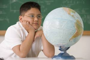 hispanic boy, hispanic boy looking at globe, hispanic boy with glasses