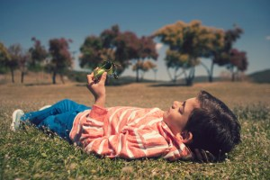 Boy holding a toy airplane lying on the grass. Selective focus image cross processed for vintage look