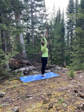 Talasana - palm pose variation - yoga pose forest yogi girl wearing black pants and bright hooded yellow sweatshirt, outdoors yoga in the woods