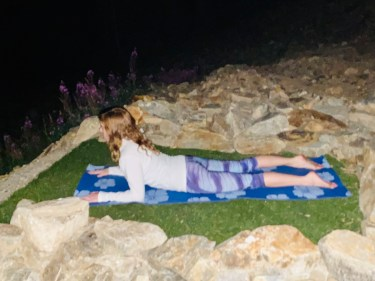 Salamba Bhujangasana - sphinx pose - yoga pose yoga at night girl wearing white long-sleeved shirt and purple pants