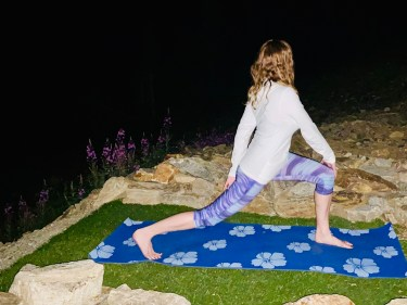 Parivrrta Ashta Chandrasana - high lunge with twist pose - yoga pose yoga at night girl wearing white long-sleeved shirt and purple pants