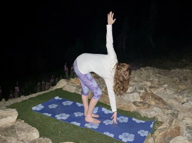Parivrrta Uttanasana - standing forward bend with twist pose - yoga pose yoga at night girl wearing white long-sleeved shirt and purple pants