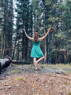 Vrksasana - tree pose - yoga pose forest yogi girl wearing green dress, outdoors barefoot yoga in the woods