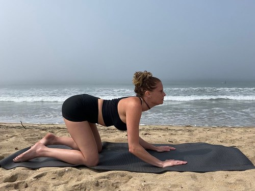 Bitilasana - cow pose - yoga pose girl sunny day yoga on the beach