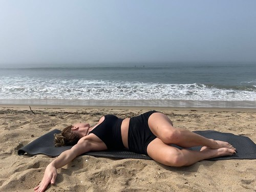 Jathara Parivartanasana - reclined twist - yoga pose girl sunny day yoga on the beach