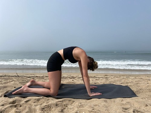Marjaryasana - cat pose - yoga pose girl sunny day yoga on the beach