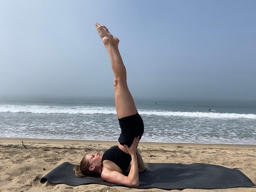 Salamba Sarvangasana - supported shoulder stand pose - yoga pose girl sunny day yoga on the beach