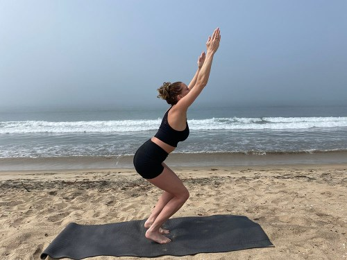 Utkatasana - powerful chair pose variation - yoga pose girl sunny day yoga on the beach
