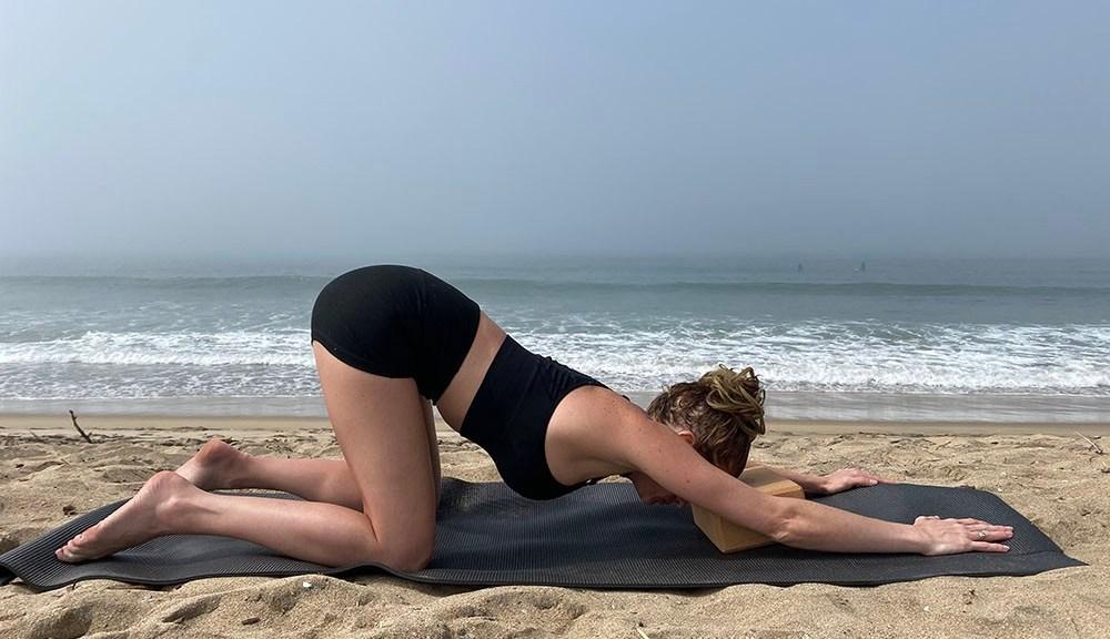 Uttana Shishosana - extended puppy melting heart pose with block - yoga pose girl sunny day yoga on the beach