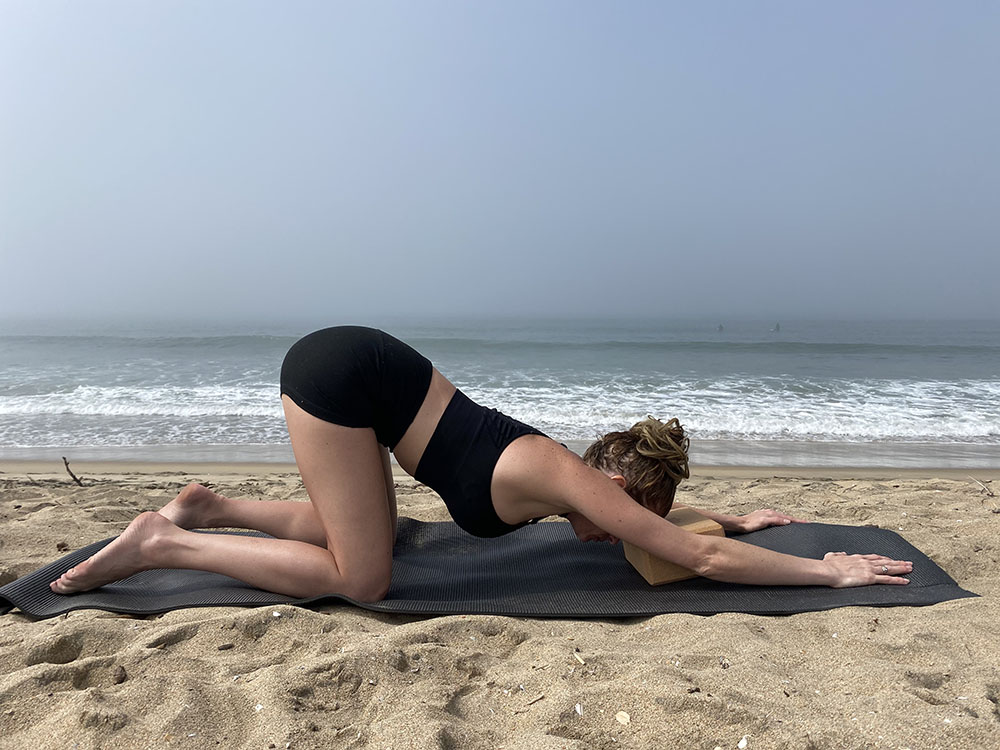 Uttana Shishosana - extended puppy melting heart pose with block - yoga pose girl sunny day yoga on the beach