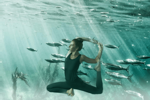 Eka Pada Rajakapotasana - mermaid pose - yoga pose girl wearing black yoga pants and tank top artsy background underwater in ocean with fish and light streaking through the water