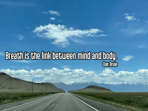 cool perspective looking down colorado highway into the mountains under a bright blue partly cloudy sky - pranayama breath breathing Quote: Breath is the link between mind and body. - Dan Brule