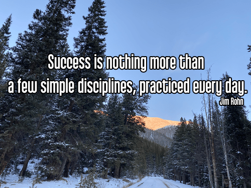 blue sky with shadowy pine trees alpine sunset reflecting pink on snow capped mountain - tapas discipline daily habits Quote: Success is nothing more than a few simple disciplines, practiced every day. - Jim Rohn