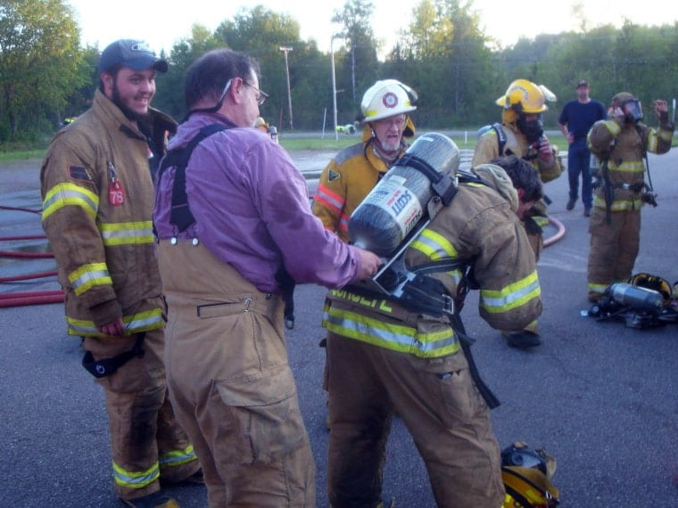 The author's husband helping fellow firefighters gear up for a live propane fire exercise.