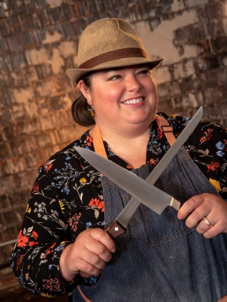 Chef Kristin Smith smiles as she holds two knives.