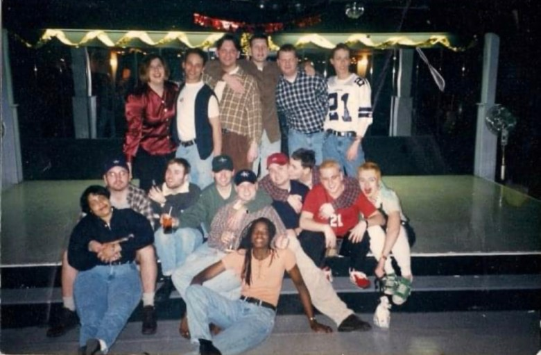 A large group of 16 gathers together for a photo inside the bar