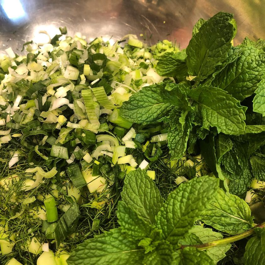 Chopped green ingredients, including cucumber, dill and mint, in a silver bowl.