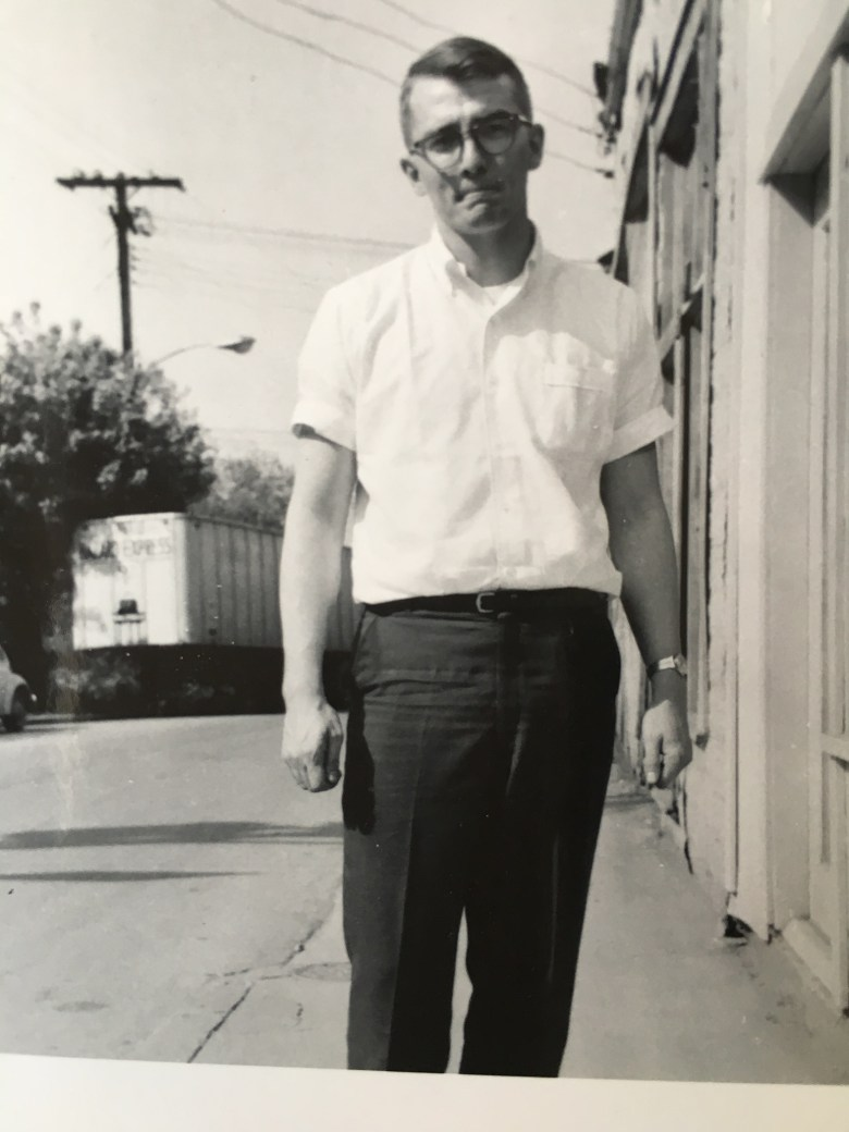 Black and white photo of a young Gurney Norman standing on the sidewalk wearing glasses, a white button-down t-shirt and dark trousers.