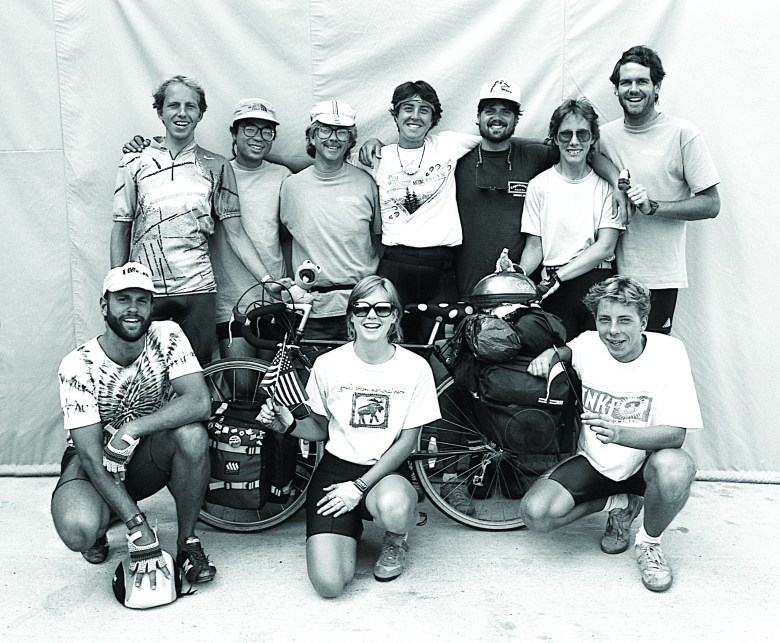 A black and white photo featuring 10 bikers embracing and posing together