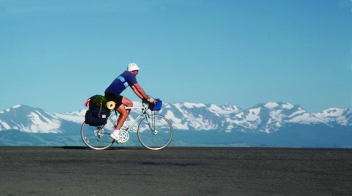 A biker crosses the horizon line from left to right against a backdrop of large mountains