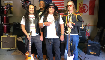 The four Blue Mountain Tribe band members stand on a stage with their instruments and wearing jeans.
