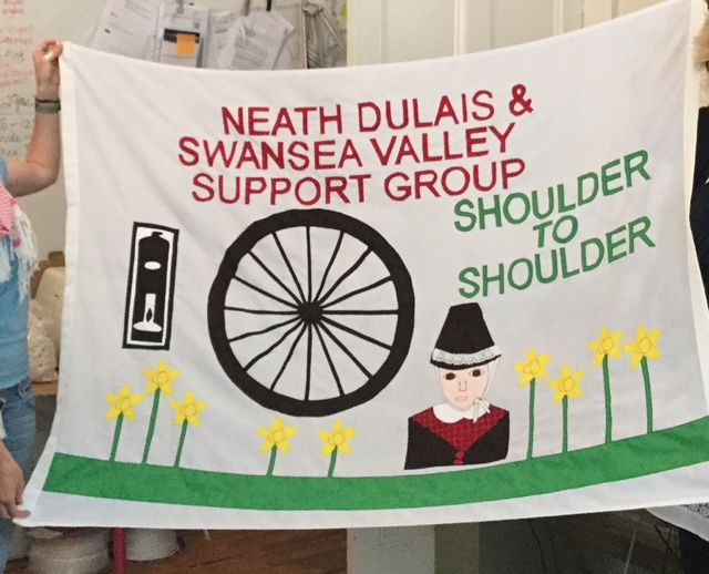 """A white banner with red and green text features a miner, yellow flowers, a wheel and the words """"Neath Dulais & Swansea Valley Support Group. Shoulder to Shoulder."""""""