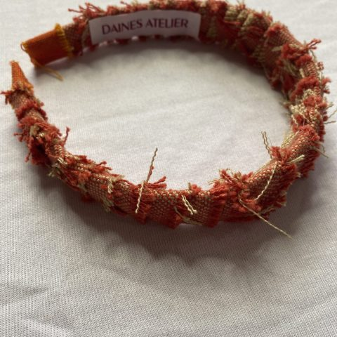 Upcycled orange wool headband with frayed edges and featuring Daines atelier label