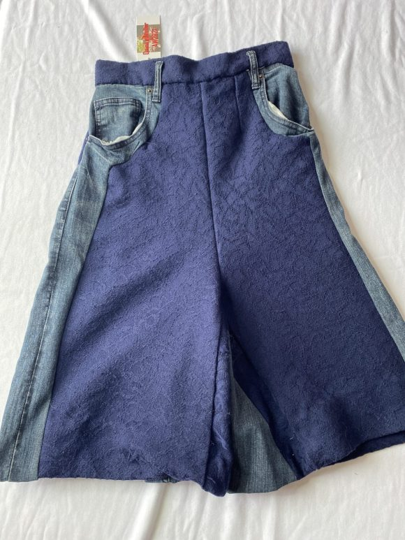 Front flatlay of vintage upcycled skirt in blue with denim panels and pockets. Culloutes shape.