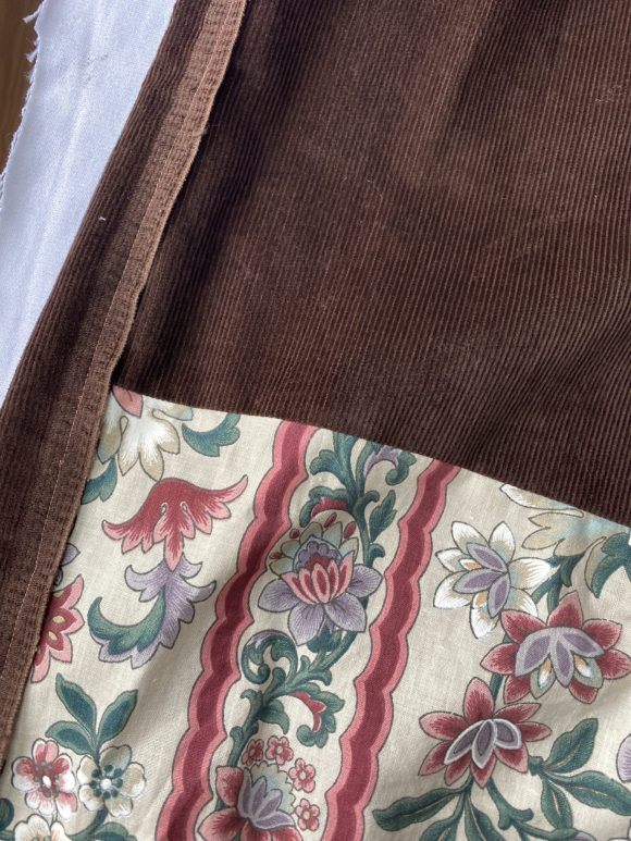 Detail shot of high waistedbrown corduroy trousers with vintage floral panel and raw selvedge edge