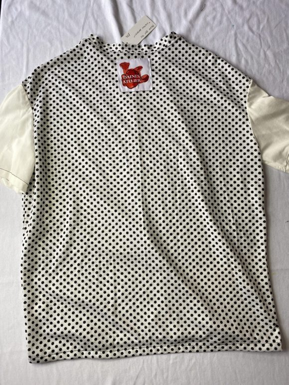 Flatlay back view of polka dot oversized tee with mismatch white sleeves and Daines atelier label branding
