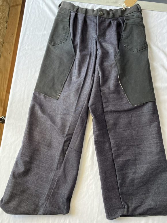 Flat lay front of upcycled and dead stock trousers. Straight leg trousers