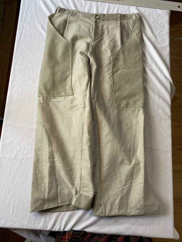 Flat lay image of front of off white trousers with a straight leg