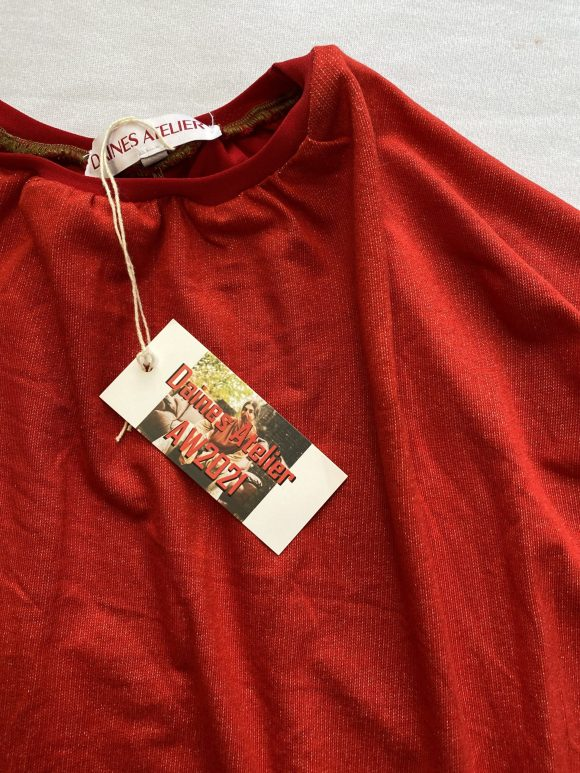 Detail shot of neck of red bat wing jumper with Daines atelier branding of cotton label and swing tag