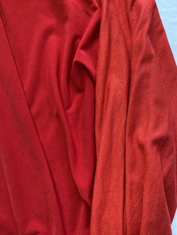 Detail shot of material of cotton red jersey batting jumper showing a slight difference in colour to sleeve body
