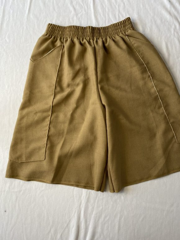 Flat lay of beige vintage linen boxing shorts with long pockets and elasticated waistband, baggy fit