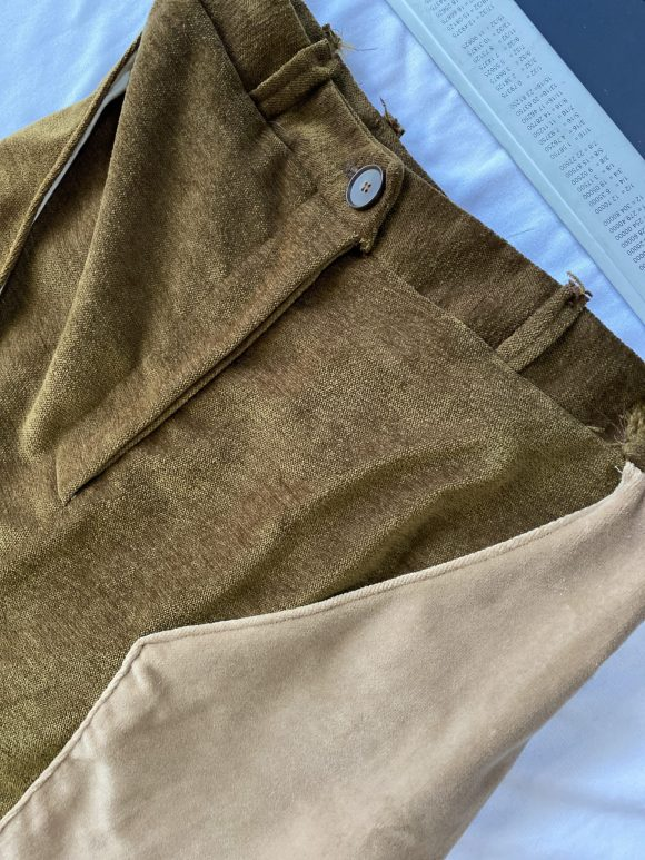 Brown corduroy trousers detail shot of button and zip fastening, belt loops with raw edges and believer pockets and their top stitching