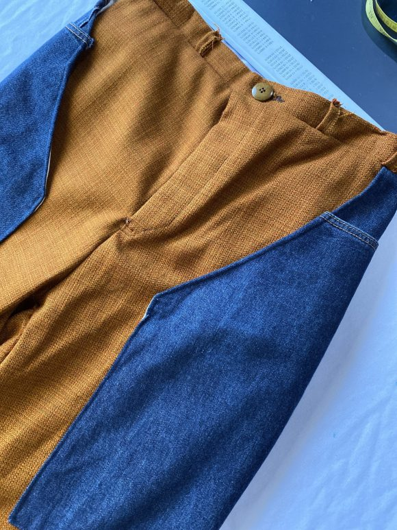 Front detail shot of button and zip fastening of orange wool dead stock trousers with upcycled denim long pockets