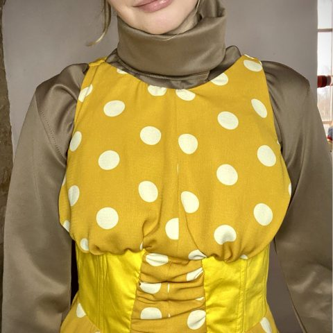 Yellow Polka dot 50s style dress with half corset In yellow cotton and bottom panel in white. Wearing the brown scuba turtleneck top