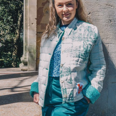 Green quilted jacket handmade in Frome from vintage French toile remnants. Martha Rice also wears a zero-waste headband, blue floral slouchy Harley vest and the green mimosa trousers. Photo by Maisie Lee Walker taken in Sydney Gardens, Bath