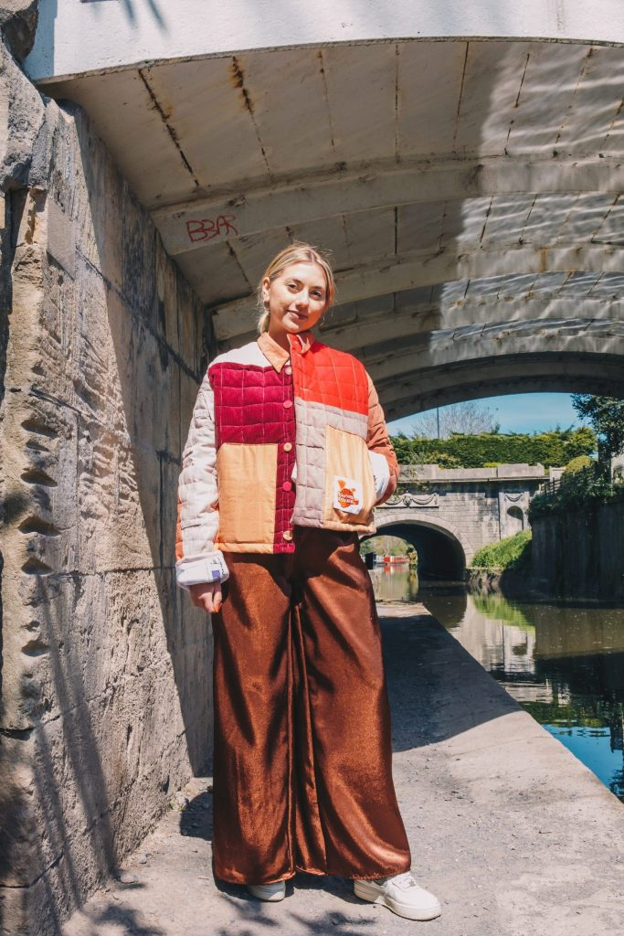 Pink Quilted Jacket made from upcycled deadstock materials in Frome, Somerset. Ella Taylor wears the mimosa trousers in brown. Photographed by Maise Lee Walker in Bath