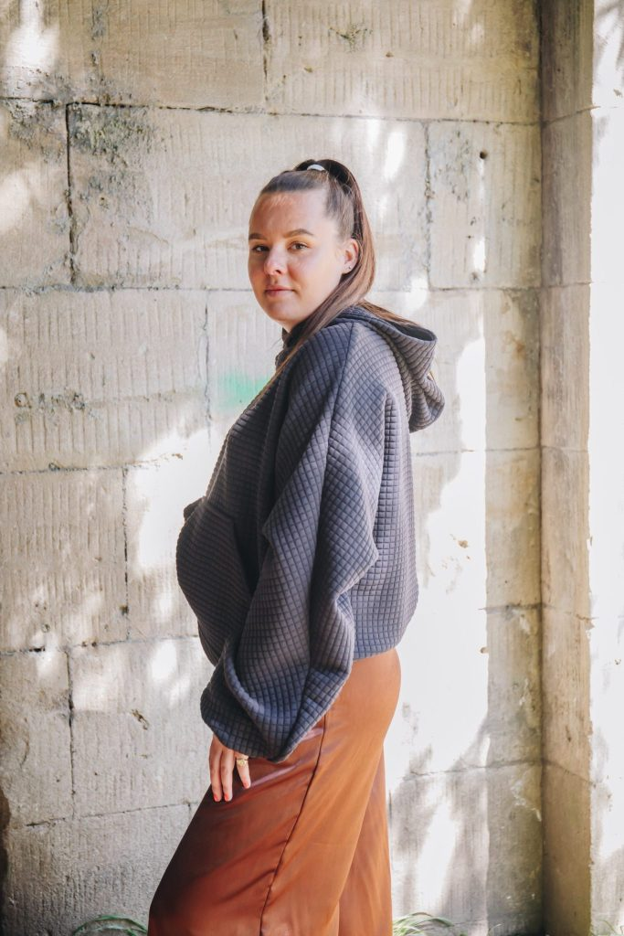 Daines Atelier quilted black hood made from dead stock materials from Amorthreads. Rosie Saunders wears the quikted batwing hoodie with brown mimosa trousers. Photograph by Maisie Lee Walker in Sydney Gardens Bath