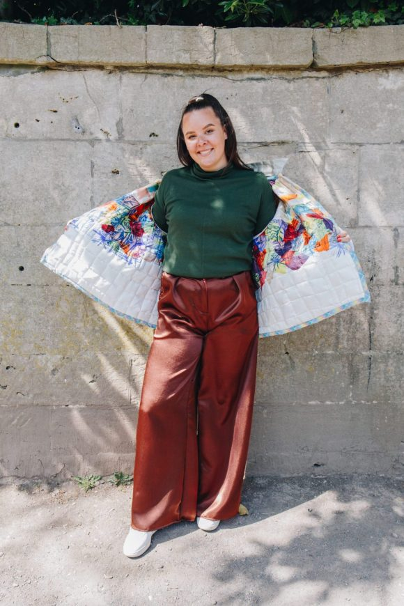 Rosie Sanders shows the lining of the beige quilted jacket wearing the green jersey turtleneck and brown mimosa trousers photograph by Maisie Lee Walker in Bath Sydney Gardens